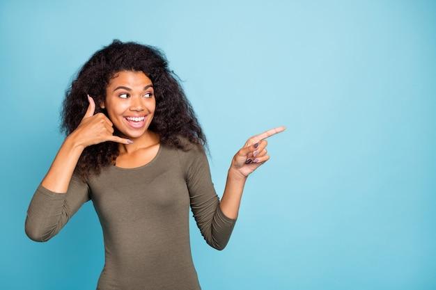 Opgelet verkoop. portret van grappig mulat meisje onder de indruk spreek met vriend via stel je voor mobiel aanbevelen promo punt wijsvinger copyspace draag groene trui geïsoleerde blauwe kleur muur