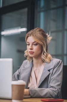 Opgelet, werk. ernstige mooie jonge vrouw met blond haar in grijze jas zitten werken aan tafel met koffie en laptop