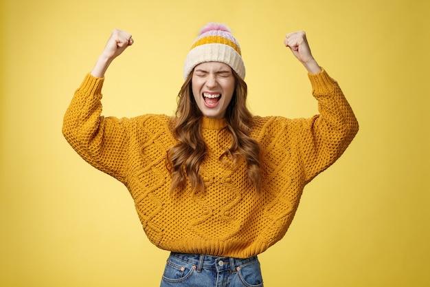 Opgelucht aantrekkelijke modieuze universiteits vrouwelijke student schreeuwen trots gebalde vuisten opheffen overwinning juichen gebaar vieren overwinning succesvolle prestatie prestatie doel, gele achtergrond