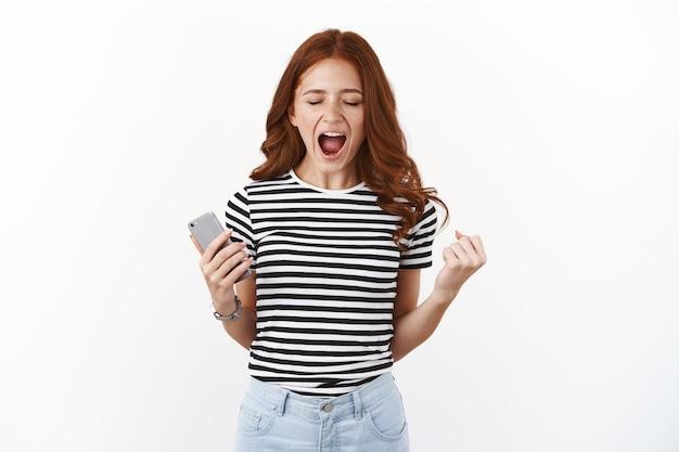 Opgelucht en blij opgewonden jonge roodharige vrouw in gestreept t-shirt, ja schreeuwen, overwinning behalen, eindelijk een beetje hard niveau, ogen dicht pompen vuist en houden smartphone volbracht, winnen