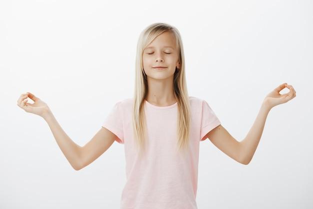 Opgelucht lachende kleine vrouw mediteren, kind probeert yoga