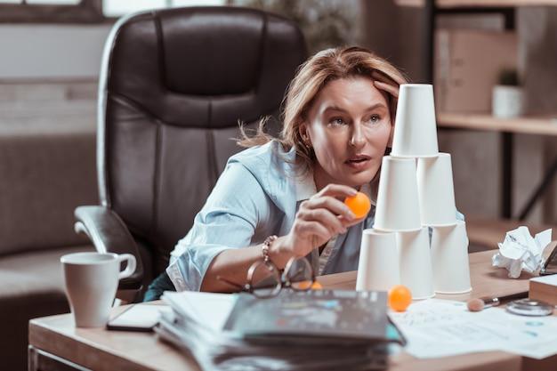 Opgelucht voelen. gestresste blonde zakenvrouw die zich opgelucht voelt bij het spelen met een tennisbal