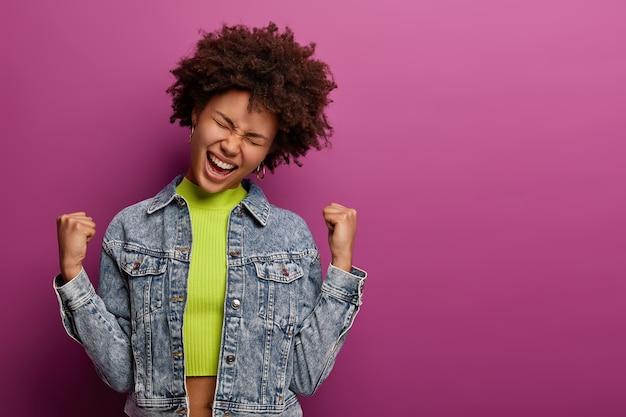 Opgelucht vrolijke afro-amerikaanse vrouw maakt vuistpomp