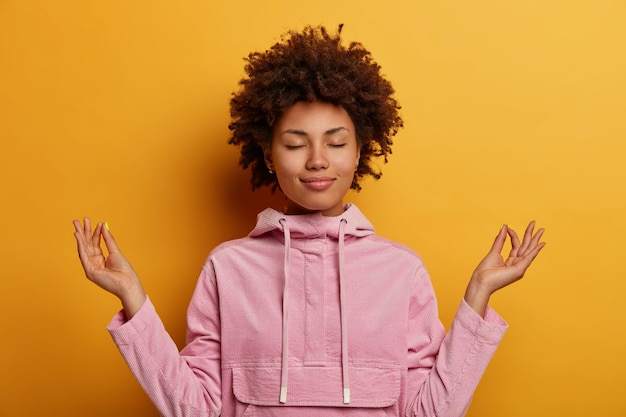 Opgeluchte etnische vrouw staat in lotushouding, probeert te mediteren tijdens quarantaine of lockdown, bereikt nirvana, doet yoga, houdt de ogen gesloten, gekleed in sweatshirt. geestelijke gezondheid, ontspanning, levensstijl