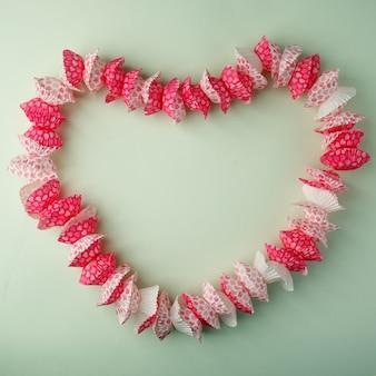 Opgemaakt in de vorm van een cupcake in de vorm van een hart op een pastelgroene achtergrond, kopie ruimte, bovenaanzicht