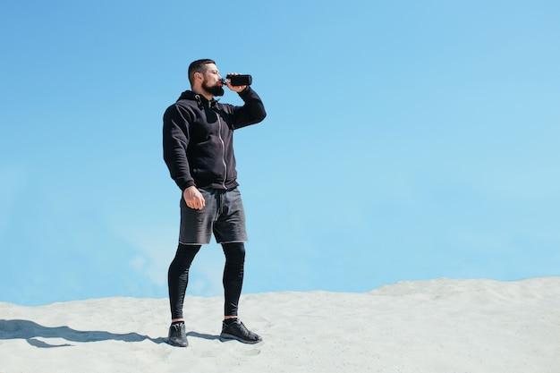 Opgepompte atleet drinkt water en rust na het joggen op een zanderige berg