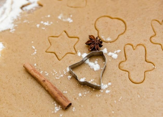 Opgerold deeg voor gemberkoekjes met uitsteekvormpjes, koekje, kaneel en kruidnagel. kookconcept.