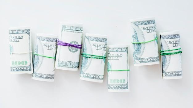 Opgerold honderd dollarrekeningen die met rubber op witte achtergrond worden gebonden