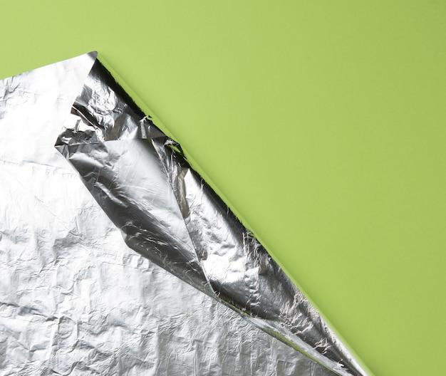 Opgerold vel folie op een groene achtergrond, de hoek is gevouwen, kopieer ruimte