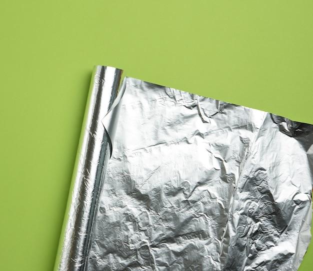 Opgerold vel folie op een groene achtergrond, de hoek is gevouwen, plat gelegd