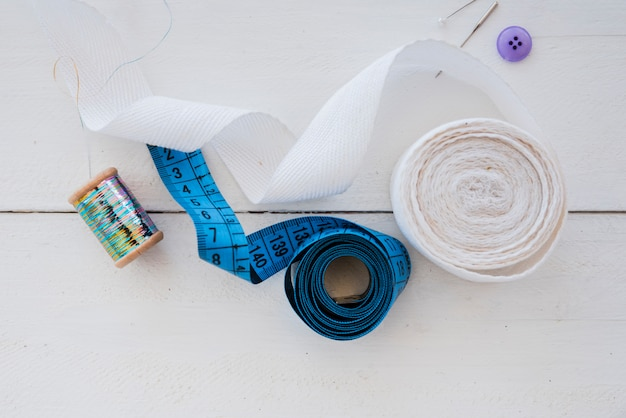 Opgerold wit lint; meetlint; knop; naald en zilveren spoel op wit houten bureau
