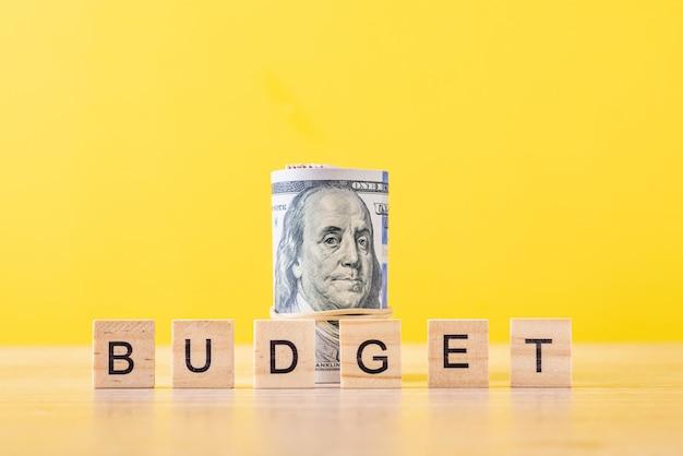 Opgerolde dollarbiljetten en woordbegroting. financieel boekhoudingsconcept