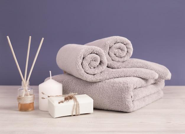 Opgerolde en gevouwen grijze badstofhanddoeken met zeep en kaarsen tegen lila muur