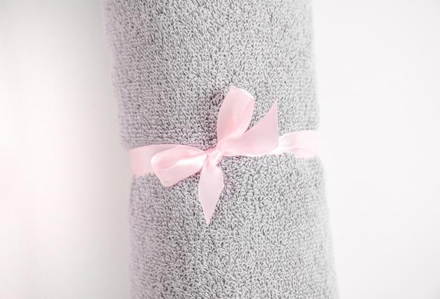 Opgerolde grijze badstof handdoek vastgebonden door roze lint tegen een witte achtergrond