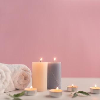 Opgerolde handdoek met verlichte kaarsen tegen roze achtergrond