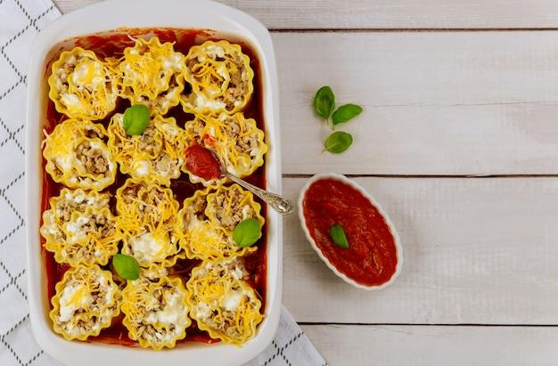Opgerolde pasta met gehakt en tomatensaus in bakplaat.