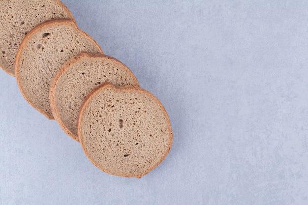 Opgestelde sneetjes zwart brood op marmeren oppervlak