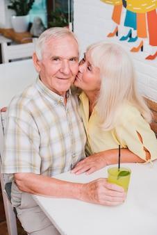 Opgetogen bejaarde echtpaar zoenen in café en genieten van een verfrissend drankje