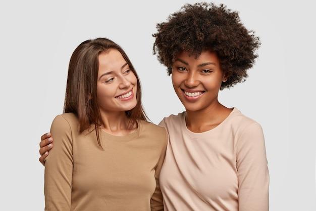 Opgetogen blije vriendinnen poseren tegen de witte muur
