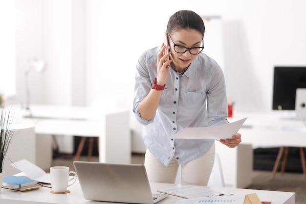 Opgetogen brunette die de telefoon in de rechterhand bij het oor houdt terwijl hij naar het document kijkt terwijl hij in de buurt van de werkplek staat