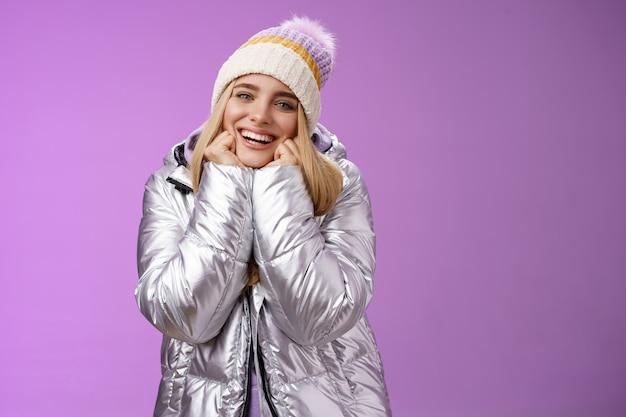 Opgetogen charmante tedere vrouw in stijlvolle schattige hoed zilveren glanzende jas magere kin handen glimlachen