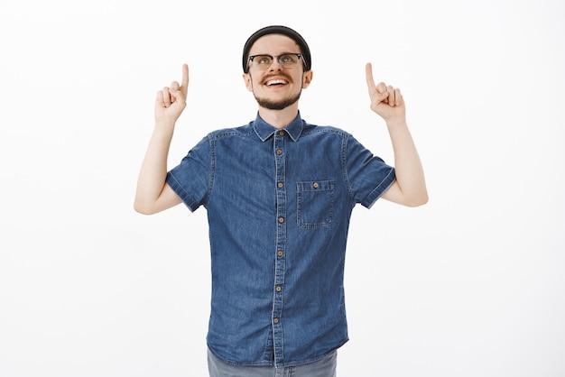 Opgetogen en tevreden knappe gecharmeerde man met baard en snor in trendy hipster-beanie en bril kijkt en wijst met een tevreden grijns naar boven, gefascineerd over grijze muur