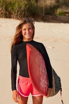 Opgetogen glimlachende tiener draagt een wetsuit of boardshort, houdt een surfplank vast