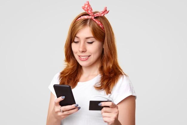 Opgetogen jonge foxy vrouw met haedband, gekleed in een casual wit t-shirt, heeft een moderne mobiele telefoon en een creditcard, maakt online betaling, verbonden met draadloos internet, geïsoleerd op een witte muur