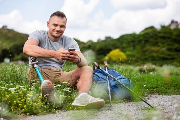 Opgetogen jonge man met een handicap die zijn telefoon gebruikt terwijl hij op het gras rust