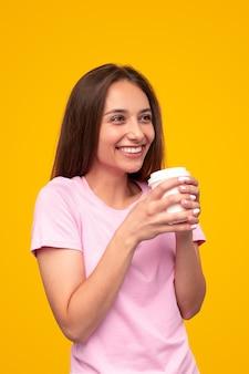 Opgetogen jonge vrouw glimlachte en kijkt weg terwijl ze geniet van verse koffie om 's ochtends tegen een gele achtergrond te gaan