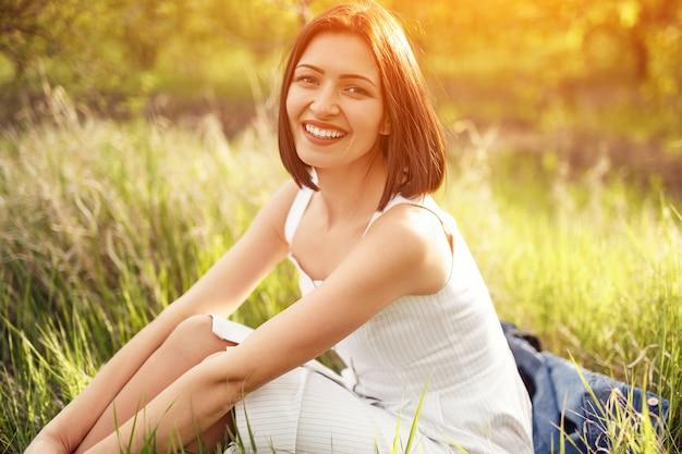 Opgetogen jonge vrouw in zomerjurk glimlachend en kijkend naar de camera terwijl ze op groen gras zit op een zonnige dag in het veld