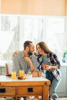 Opgetogen jongedame leunend op de schouder van een man in de keuken terwijl ze lacht