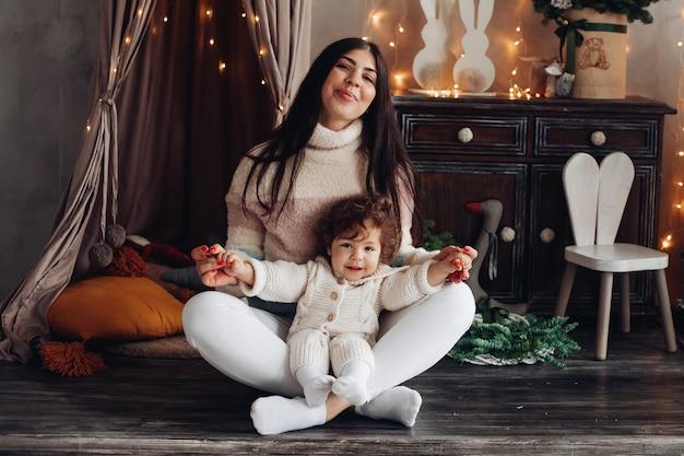 Opgetogen jongedame zittend met gekruiste benen op de vloer terwijl ze een schattig kind op haar schoot vasthoudt en glimlacht