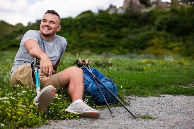 Opgetogen jongeman die op het gras rust na toeristische sportactiviteiten