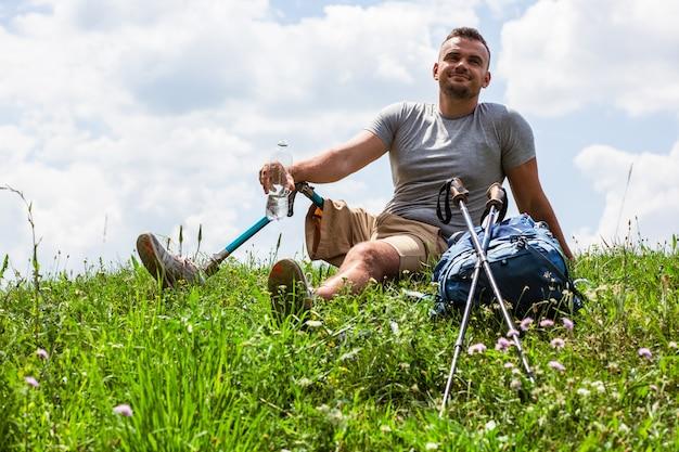 Opgetogen jongeman die rust na het herscheppen van activiteiten terwijl hij water drinkt op het gras