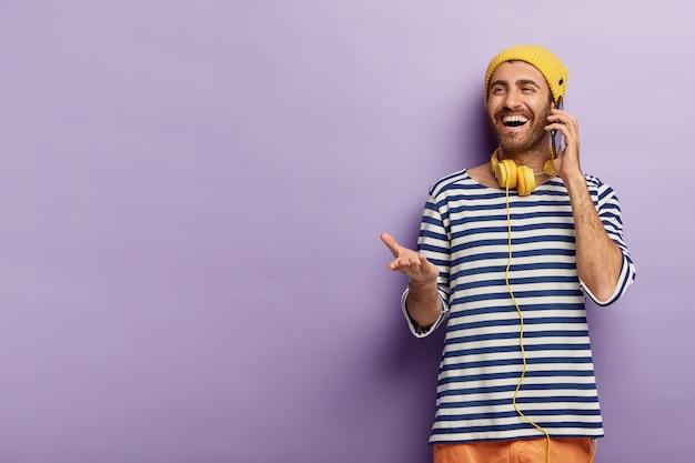 Opgetogen jongeman maakt afspraak via smartphone, praat via mobiel, steekt handpalm op, heeft blije uitdrukking, draagt gestreepte trui
