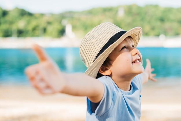 Opgetogen jongen die handen uitspreidt en omhoog in daglicht kijkt