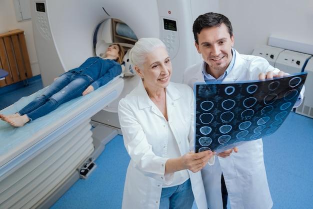 Opgetogen knappe aardige man die met zijn collega staat en een ct-scanbeeld onderzoekt terwijl hij samenwerkt