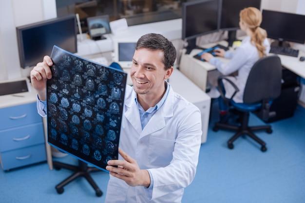 Opgetogen knappe ervaren arts die de hersenfoto vasthoudt en gelukkig is terwijl hij de positieve effecten van de behandeling ziet