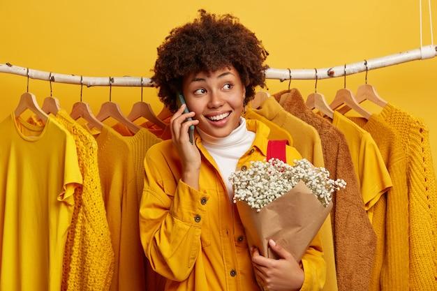 Opgetogen krullende vrouw wendt zich af, belt via mobiel, deelt indrukken na een winkeldag, poseert met een boeket bloemen