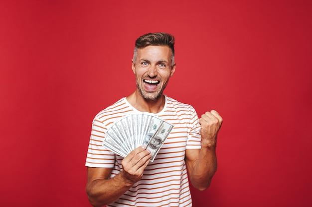 Opgetogen man in gestreept t-shirt glimlachend en met fan van geld in contanten geïsoleerd op rood