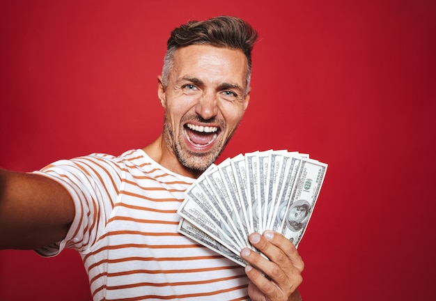 Opgetogen man in gestreept t-shirt glimlachend en selfie nemend terwijl hij een fan van geldbankbiljetten vasthoudt die op rood zijn geïsoleerd