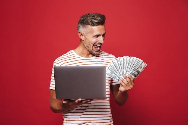 Opgetogen man in gestreept t-shirt glimlachend terwijl hij een fan van geldbankbiljetten en een laptop vasthoudt die op rood is geïsoleerd