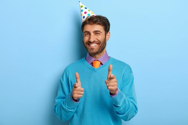 Opgetogen man met verjaardagshoed poseren in blauwe trui