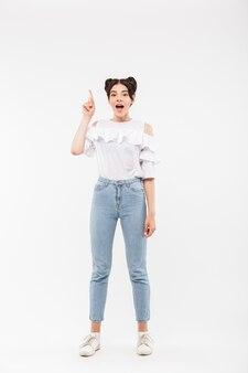 Opgetogen meisje met dubbele broodjes kapsel wijzende vinger omhoog naar copyspace of betekenis hebben idee, geïsoleerd op wit