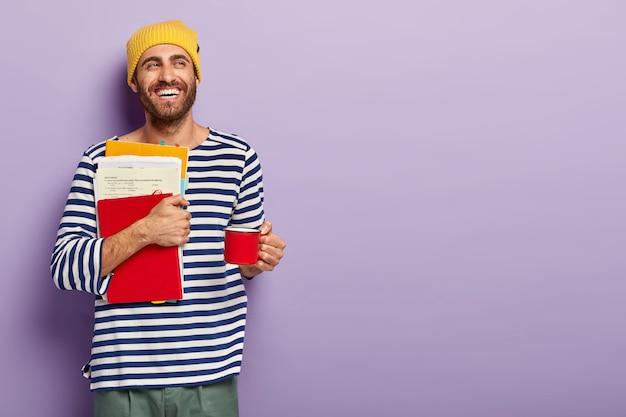 Opgetogen ongeschoren jongeman student houdt papieren en rode blocnote, houdt beker met warme drank, heeft koffiepauze, in goed humeur, kijkt opzij met brede glimlach, geïsoleerd op paarse achtergrond