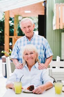 Opgetogen oud paar die in koffie op terras koesteren die van verfrissende drank en cake genieten