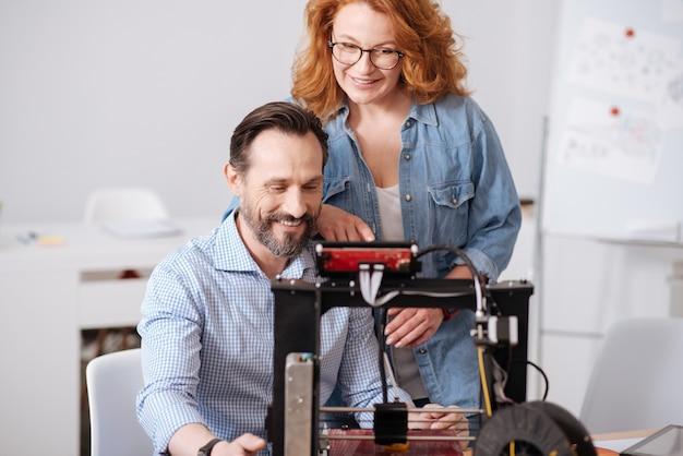 Opgetogen professionele 3d-ontwerpers die glimlachen en naar de 3d-printer kijken terwijl ze samenwerken