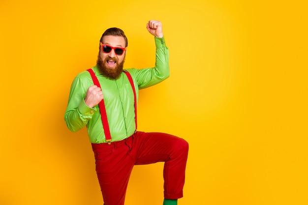 Opgetogen vrolijke gelukkige man bereiken ongelooflijke doel win schreeuw ja vuisten heffen dragen broek broek geïsoleerd over glans kleur