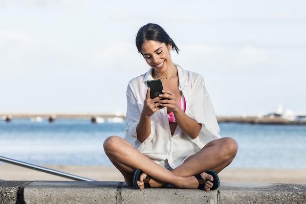 Opgetogen vrouw die mobiele telefoon op dijk gebruiken